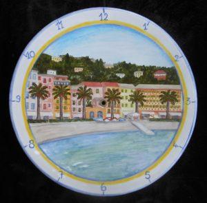 Piatto orologio con veduta cittadina di riviera, dipinto a mano